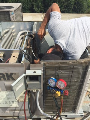 Reuben fixes a refrigerant leak on a York condenser during an air conditioning repair in Tracy