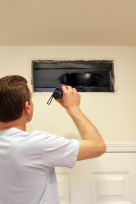 Tracy air duct cleaning specialist surveys a wall duct