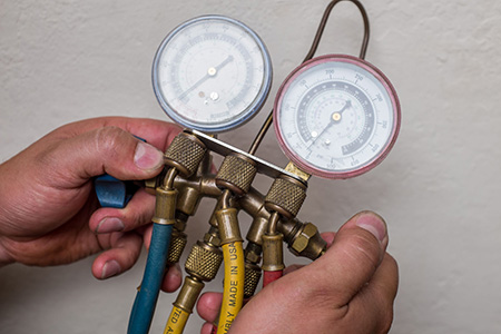 Ceres HVAC technician checks ac refrigerant levels with specialized pressure gauge
