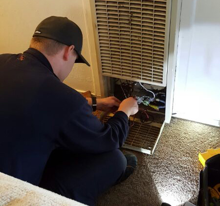 Furnace repair technician checks faulty wiring