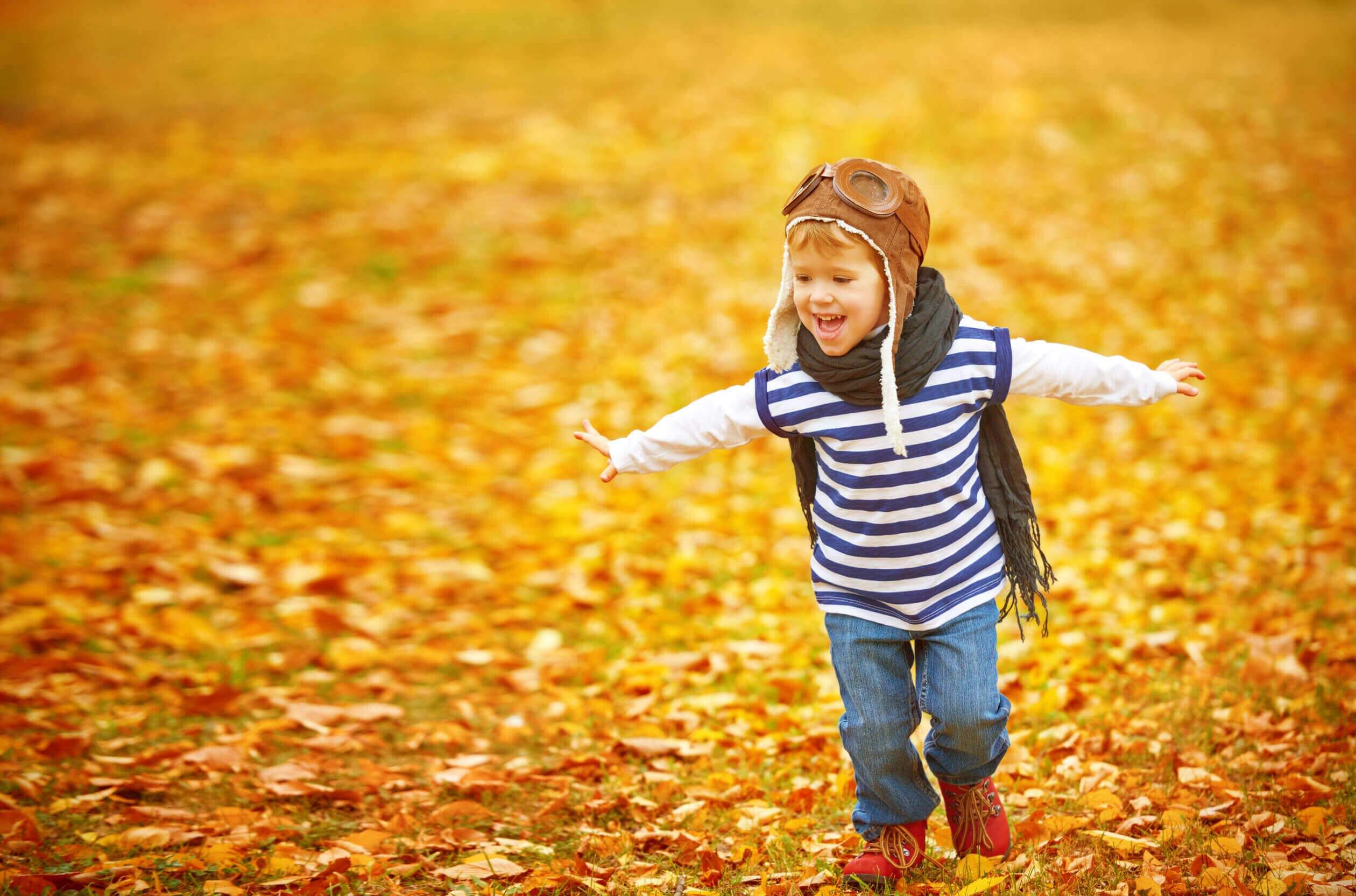 Child with scarf runs through leaves in fall