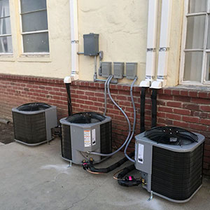Three ac condensers installed outside a multi-family housing complex in Modesto