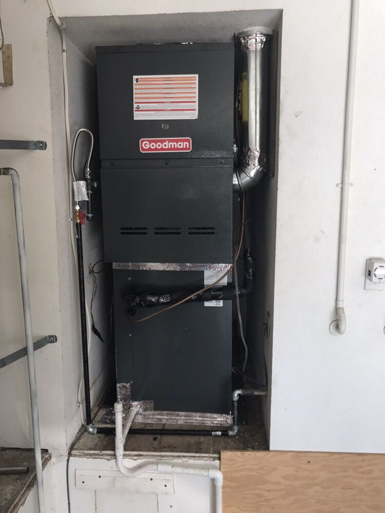 5 ton Goodman brand furnace being installed into a space in the wall.