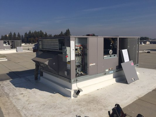 a new dark gray start up HVAC package unit being installed on a commercial building in Oakdale, ca