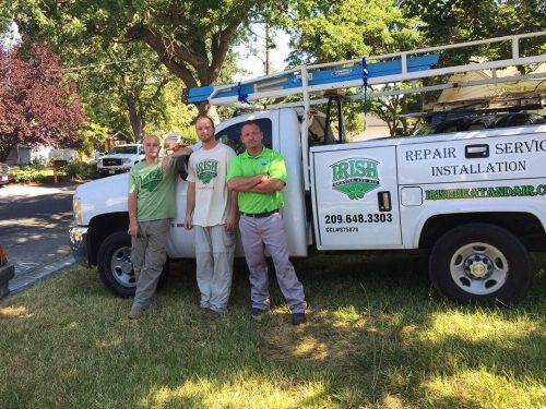 Ryyan Murphy the owner of irish heating and air conditioning standing with two employees in front of the white company truck