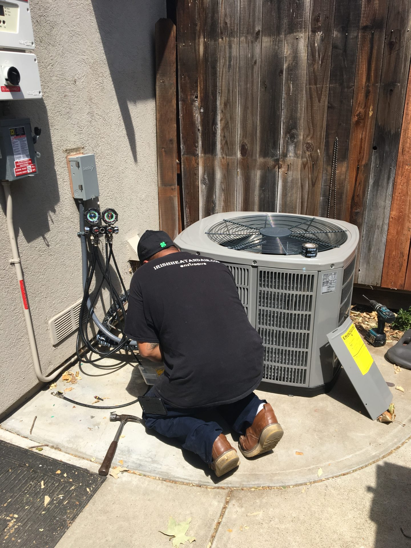 professional irish heating and air hvac technician repairing residential ac unit on the side of house near fence