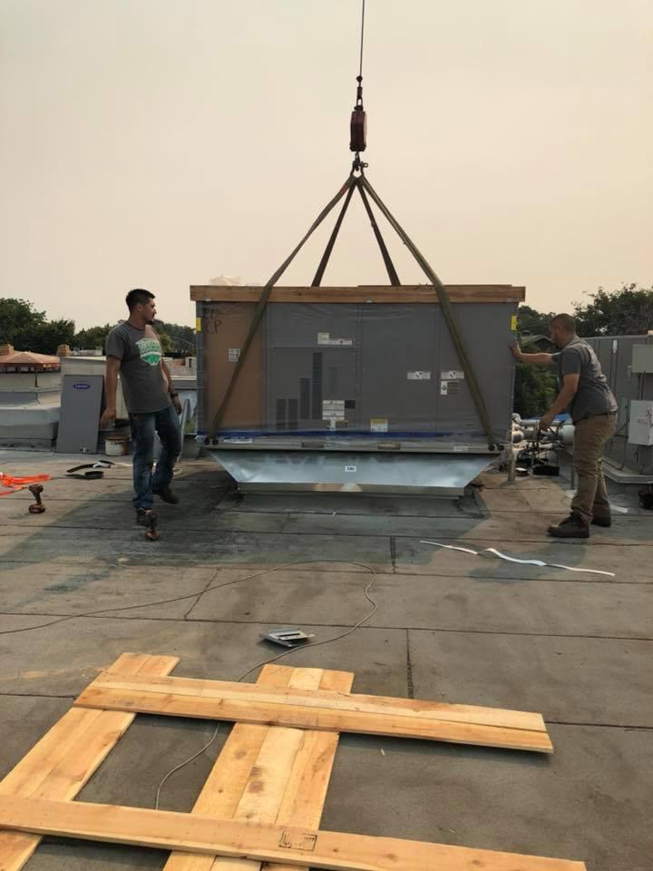 Commercial packaged HVAC system installation via crane on shopping center in Modesto